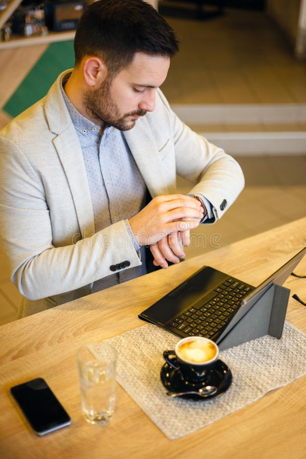 Lyckad ung affärsman som ser hans klocka som arbetar i kafé arkivfoto
