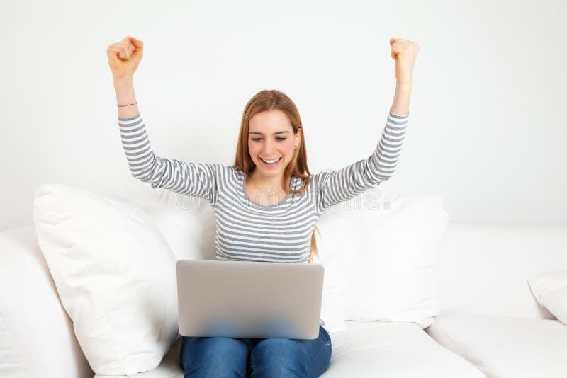 Lyckad ung kvinna med anteckningsboken på en soffa royaltyfri fotografi