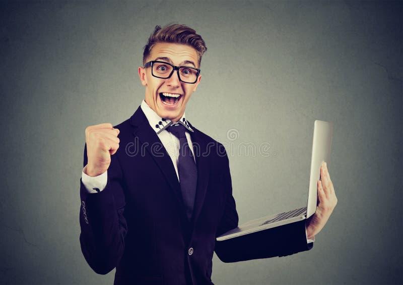 Lyckad ung man som använder bärbara datorn som bygger online-affären som firar framgång fotografering för bildbyråer