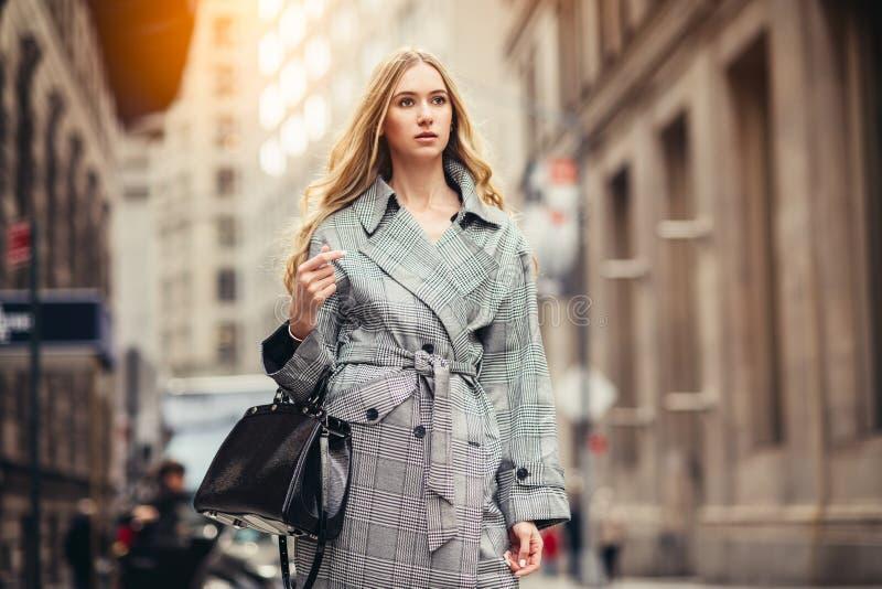 Lyckad ung vuxen affärskvinna med den svarta påsen som går till jobbet på den New York City gatan på det finansiella området arkivbild