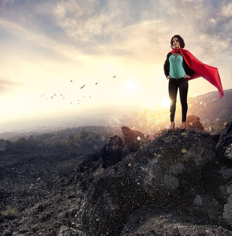 Lyckade affärskvinnahandlingar som en toppen hjälte på ett berg Begrepp av beslutsamhet och framgång arkivbild