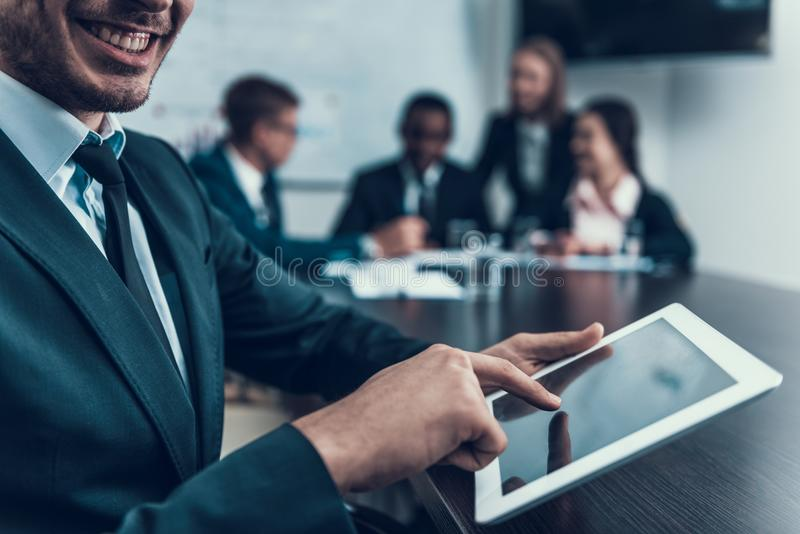 Lyckade affärsmanpunkter fingrar på datorminnestavlaskärmen i konferensrum var möte är royaltyfri fotografi