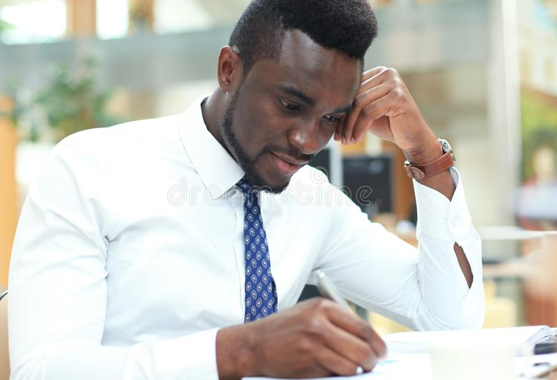 Lyckade anmärkningar för afrikansk amerikanaffärsmanhandstil i papper, sammanträde på hans rymliga kontor royaltyfria bilder