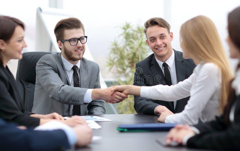 Lyckade businesspeople som skakar händer i ett modernt kontor arkivbilder