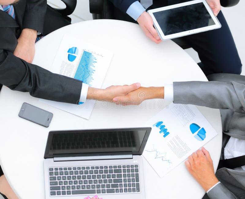 Lyckade businesspeople som skakar händer i ett modernt kontor arkivfoton