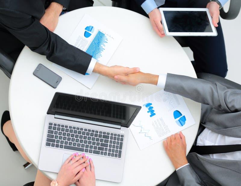 Lyckade businesspeople som skakar händer i ett modernt kontor royaltyfri bild