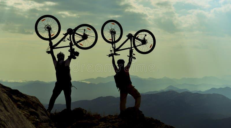 Lyckade cyklister på maximumet av berget royaltyfri foto