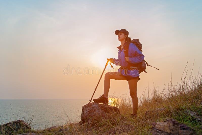 Lyckade fotvandrarekvinnor som fotvandrar med ryggsäcken som överst står av berget och tycker om dalsikt fotografering för bildbyråer