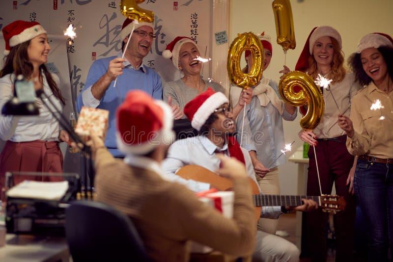 Lyckade kollegor i jultomtenlock som har julgyckel arkivbilder