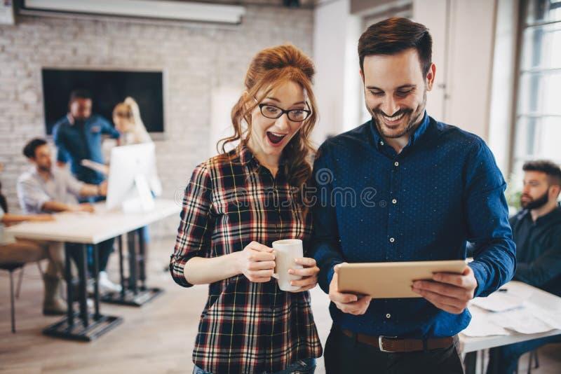 Lyckade lyckliga coworkers som meddelar i företagskontor royaltyfria foton