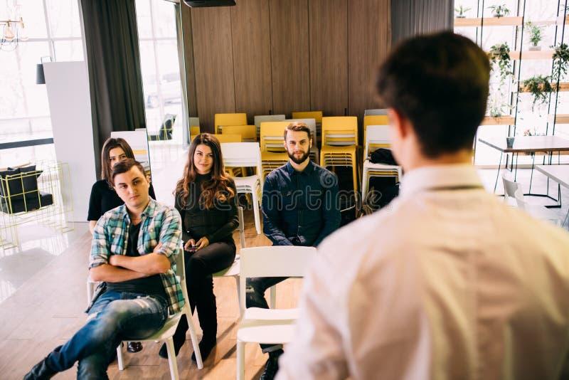 Lyckade unga businesspeople som har möteutbildning i modernt kontor Baksida-sikt av högtalaren nära whiteboard royaltyfria bilder