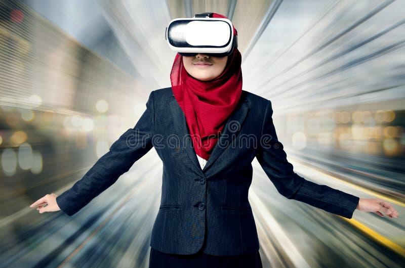 Lyckade unga muslimahaffärskvinnor som bär virtuell verklighethörlurar med mikrofon över abstrakt bakgrund för dubbel exponering arkivfoto