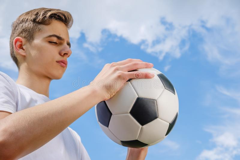 Lyckafotbollsspelare med bollen och bl? himmel royaltyfri fotografi