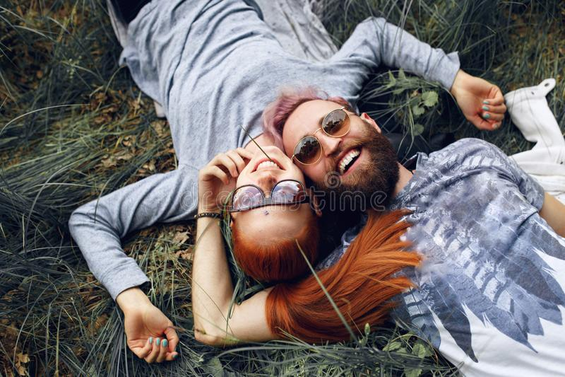 Lyckahipsterpar, i solglasögon, röd haired kvinna och skäggig man som placeras ner på ett grönt gräs arkivfoto