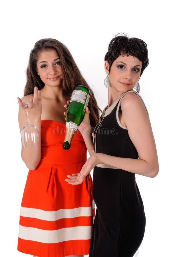 Lyckakvinnor som rymmer exponeringsglas och flaskan royaltyfri foto