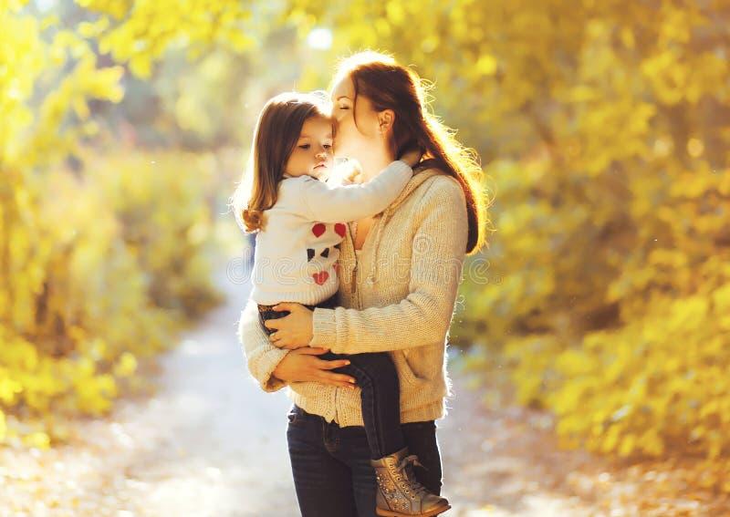 Lyckamoder! Kyssande barn för mamma i solig höst royaltyfri foto