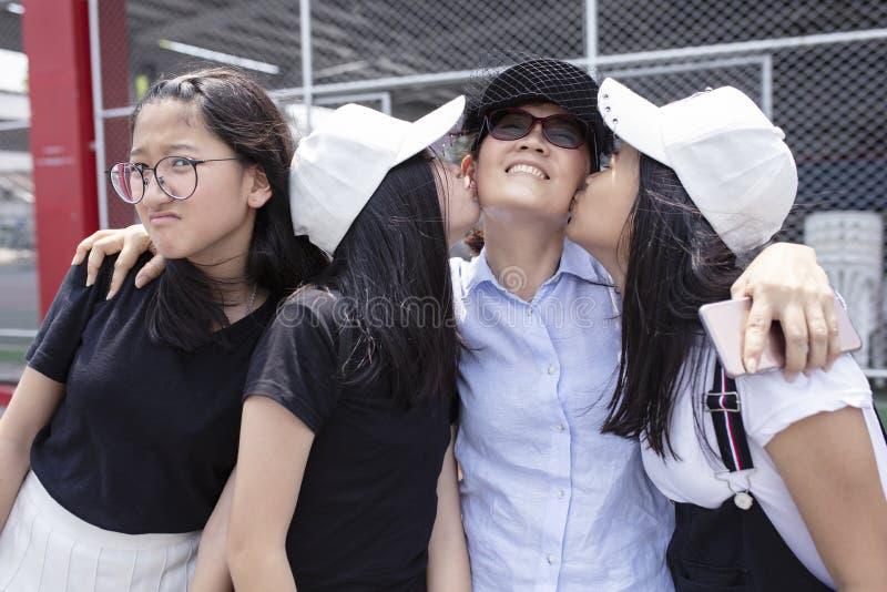 Lyckasinnesrörelse av asiatisk teenger som kysser på lyckaframsida av kvinnan arkivfoto