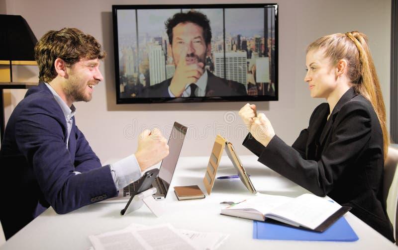 Lyckat affärsfolk i konferenssamtalet som är lycklig om avtalssned bollskott arkivfoto