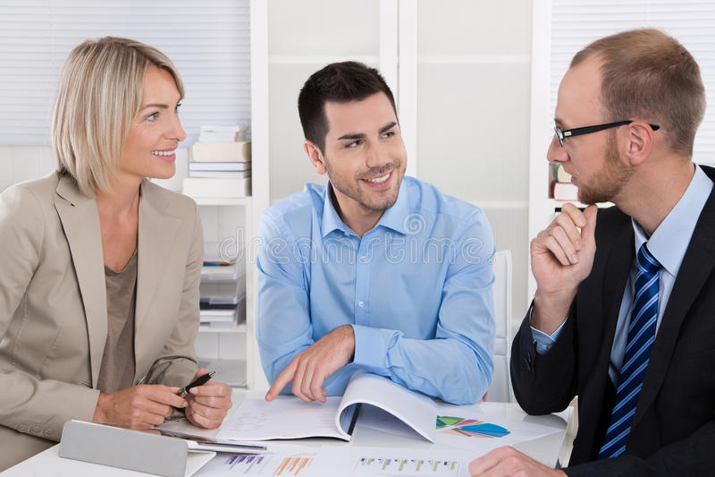 Lyckat affärslagsammanträde runt om en tabell i ett möte arkivfoton