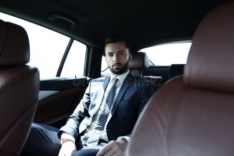 Lyckat affärsmansammanträde i baksätet av en bil royaltyfri fotografi