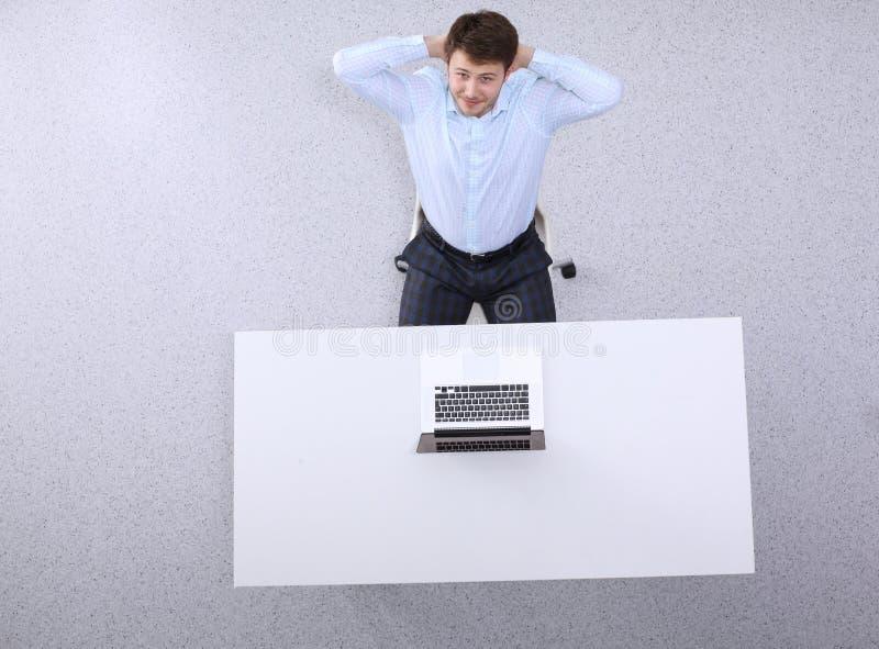 Lyckat affärsmansammanträde som tillbaka kopplar av i hans stol på kontoret med hans händer bak hans huvud royaltyfria foton