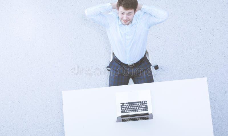Lyckat aff?rsmansammantr?de som tillbaka kopplar av i hans stol p? kontoret med hans h?nder bak hans huvud arkivbild