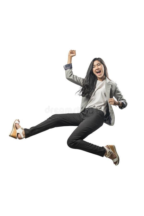 Lyckat asiatiskt hoppa för affärskvinna och lyftt arm till luften arkivbild