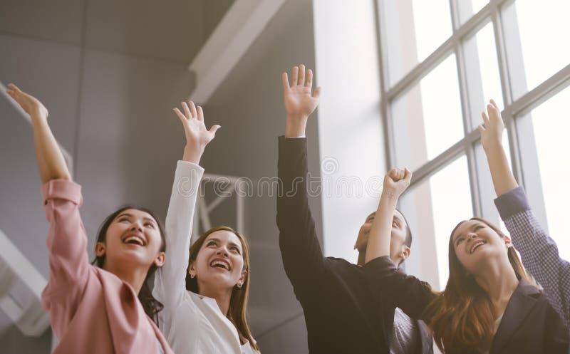 Lyckat av affärsfolk som i regeringsställning firar Grupp av lyckliga affärslaghänder som lyfts för framgång och att segra arkivbilder
