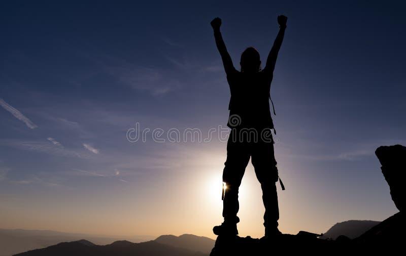 Lyckat, beslutsamt och beslutsamt Bergsbestigninghjälp på vaggar arkivfoton
