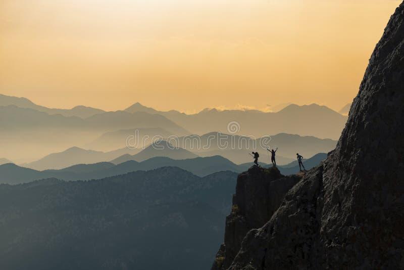 Lyckat, beslutsamt och utmanande folk upptill av bergen royaltyfri bild