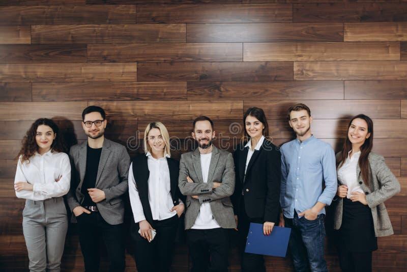 Lyckat företag med lyckliga arbetare som står i rad i modernt kontor royaltyfria foton