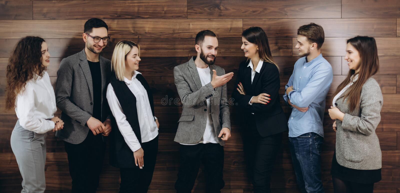 Lyckat företag med lyckliga arbetare som står i rad i modernt kontor arkivbild