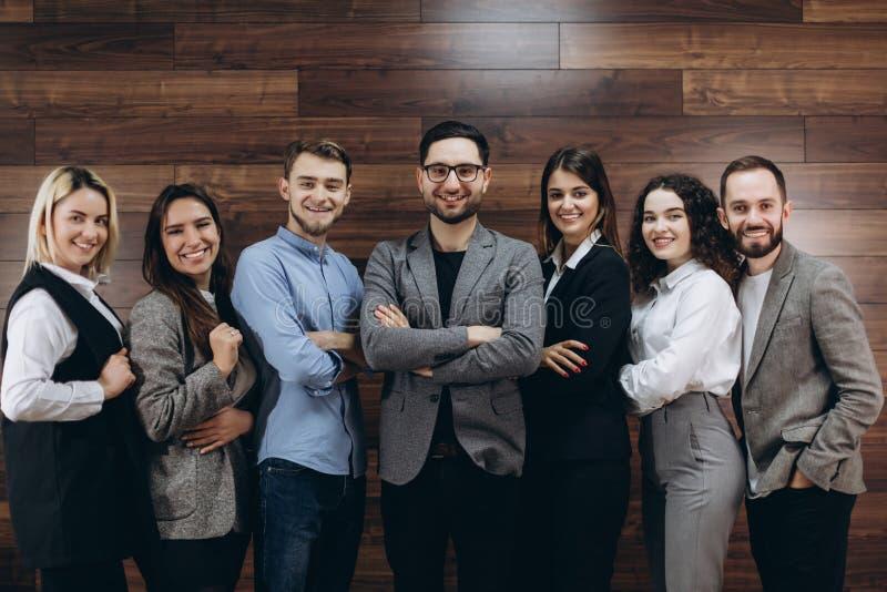 Lyckat företag med lyckliga arbetare som står i rad i modernt kontor arkivfoto