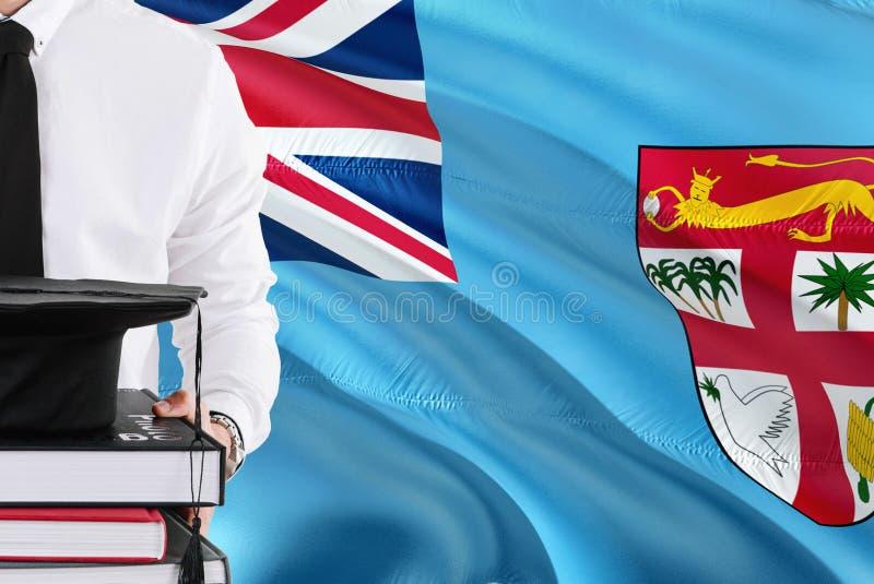 Lyckat Fijian studentutbildningsbegrepp Hållande böcker och avläggande av examenlock över fijiansk flaggabakgrund royaltyfria bilder