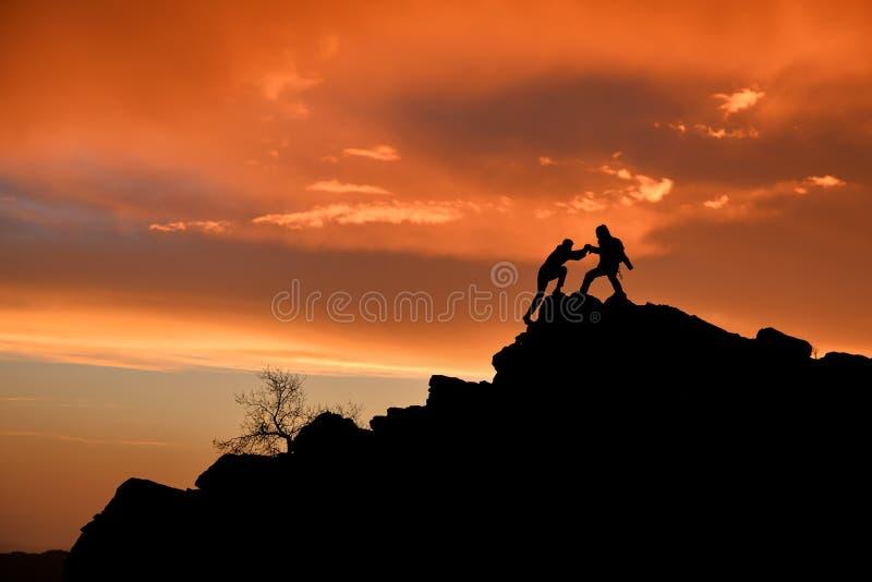 Lyckat folk som utmanar & klättra i berg hjälp royaltyfria foton