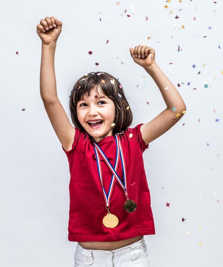 Lyckat härligt barn som skrattar med mästaremedaljer som firar över confettis royaltyfria bilder