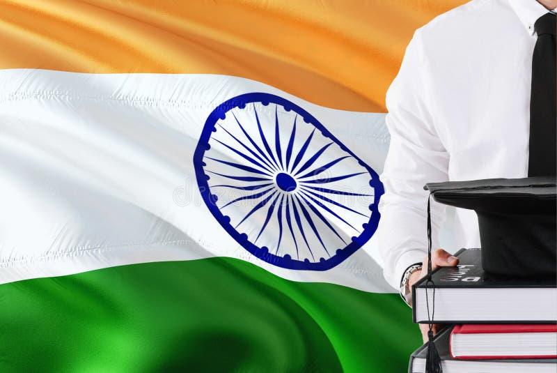 Lyckat indiskt studentutbildningsbegrepp Hållande böcker och avläggande av examenlock över Indien flaggabakgrund royaltyfri foto