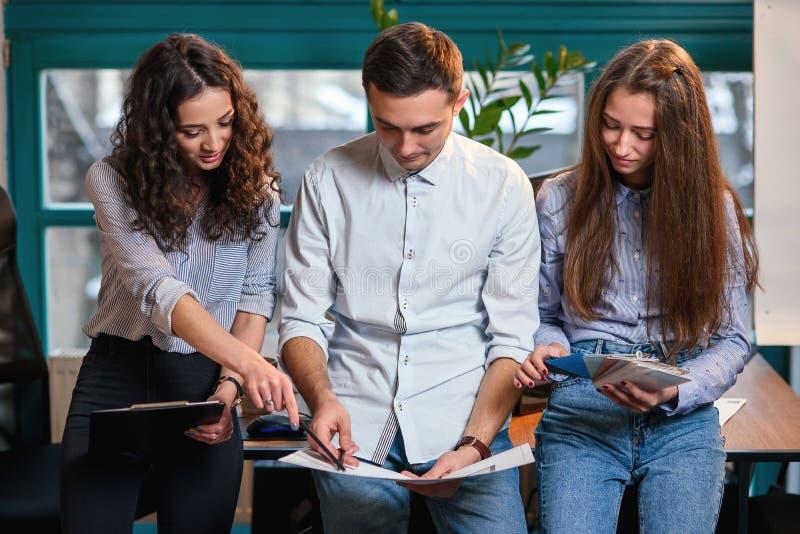 Lyckat lag av det unga caucasian teknikeranseendet nära trätabellen och samtal om nytt projekt äganderätt för home tangent för af royaltyfri bild
