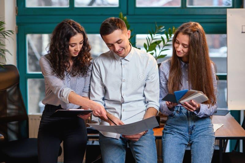 Lyckat lag av det unga caucasian teknikeranseendet nära trätabellen och samtal om nytt projekt äganderätt för home tangent för af royaltyfria bilder