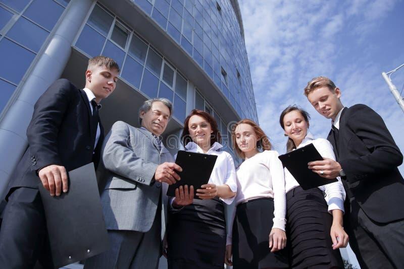 Lyckat lag för affärsfolk som tillsammans utomhus står nära modern kontorsbyggnad arkivbild