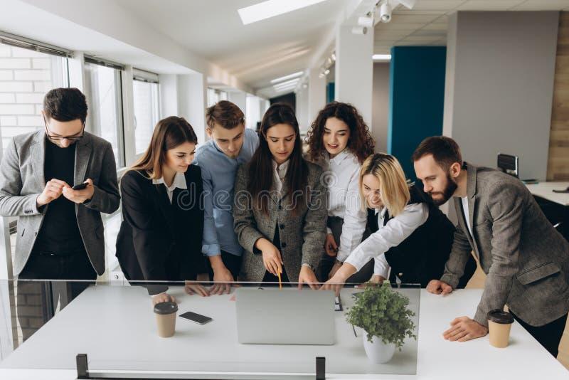 Lyckat lag Grupp av ungt affärsfolk som tillsammans arbetar och meddelar i idérikt kontor arkivfoto