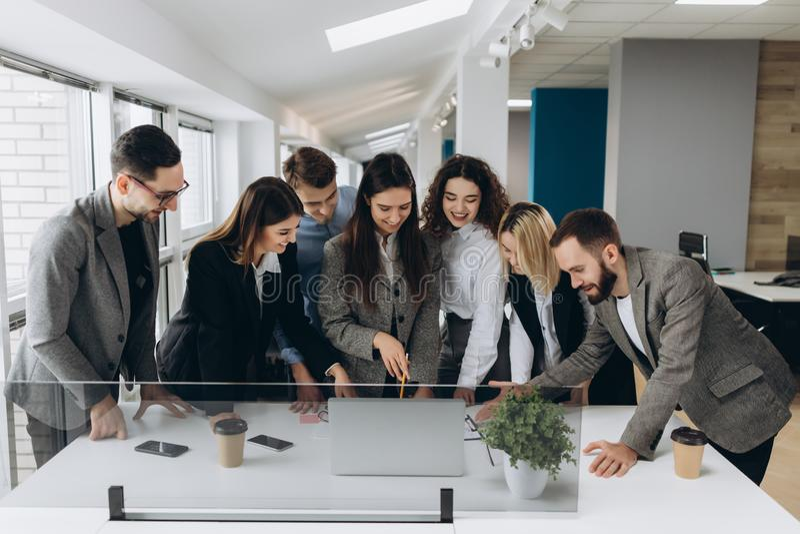 Lyckat lag Grupp av ungt affärsfolk som tillsammans arbetar och meddelar i idérikt kontor fotografering för bildbyråer