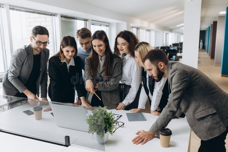 Lyckat lag Grupp av ungt affärsfolk som tillsammans arbetar och meddelar i idérikt kontor arkivbilder
