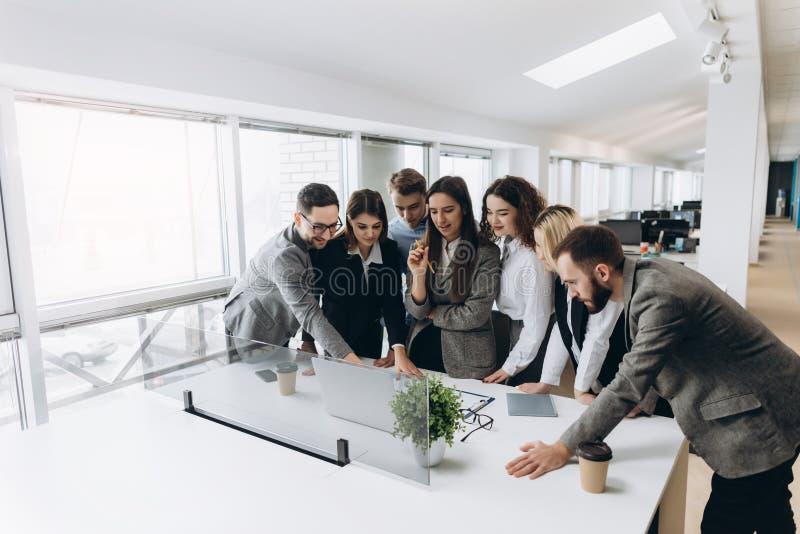 Lyckat lag Grupp av ungt affärsfolk som tillsammans arbetar och meddelar i idérikt kontor arkivbild