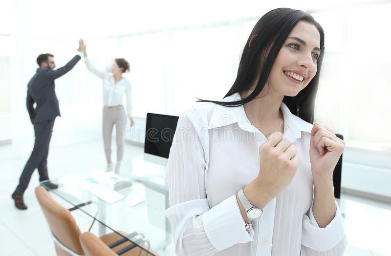 Lyckat lyckligt sammanträde för affärskvinna på skrivbordet fotografering för bildbyråer