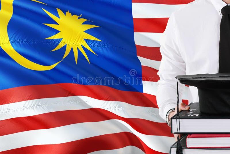 Lyckat malaysiskt studentutbildningsbegrepp Hållande böcker och avläggande av examenlock över Malaysia flaggabakgrund royaltyfri illustrationer