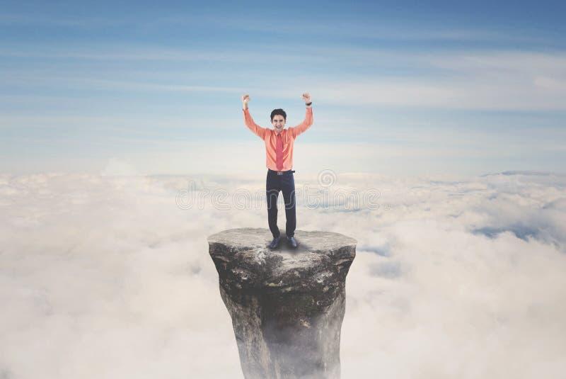 Lyckat manligt entreprenöranseende på berget royaltyfri fotografi