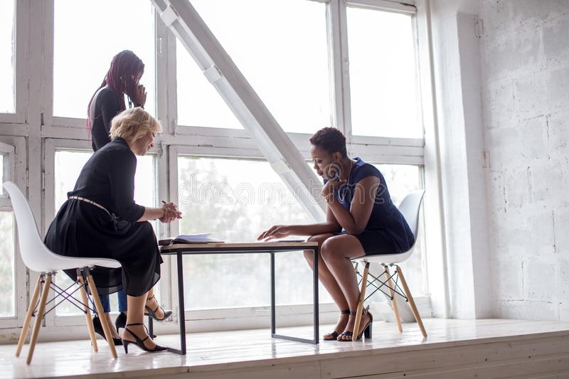 Lyckat multietniskt kvinnligt lag i coworking utrymme Öppet utrymmekontor royaltyfria foton