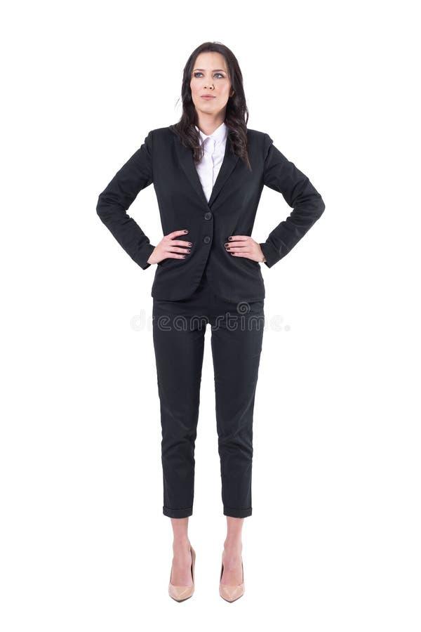 Lyckat säkert affärskvinnachefanseende med armar på höfter som ser upp royaltyfri foto