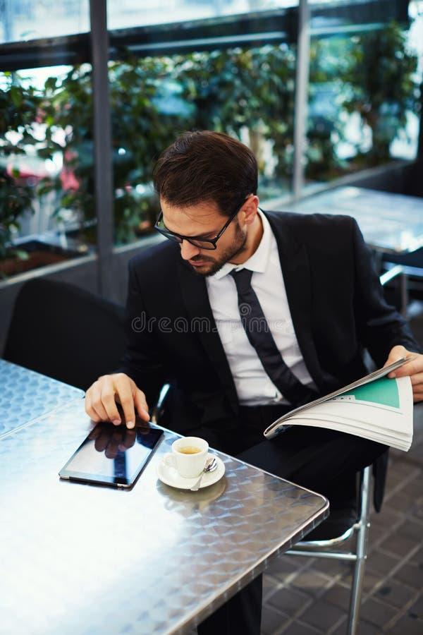 Lyckat sammanträde för den unga mannen på terrassen av en restaurang och gör plan för dagen royaltyfri fotografi